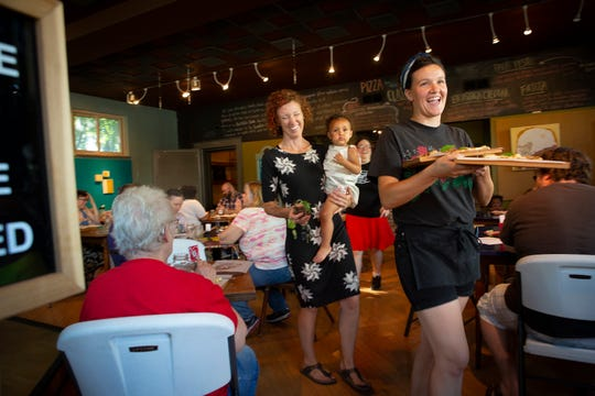 Lyric Morris-Latchaw (far right) walks out of Moriah Pie in Norwood, Ohio, on Friday, July 12, 2019, to serve pizza to customers listening to music across the street while Erin Lockridge (center) and daughter Amarie follow.