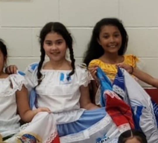A cropped image of a group photo showing members of a Latina heritage dance club in Des Moines. Grecia Daniela Alvarado-Flores, left, stands next to her friend Nelly Orellana. Alvarado-Flores was just 11 when she was killed, along with her mother and 5-year-old brother, Tuesday, July 19, 2019,  in Des Moines.