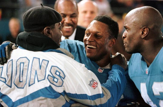 Detroit Lions' Barry Sanders, center, is congratulated by his father William and teammate Ryan Stewart, right, following their game with the New York Jets, Dec. 21, 1997, in Pontiac. Sanders became only the third player in NFL history to rush for 2,000 yards in a season, running for 184 yards and the winning touchdown.