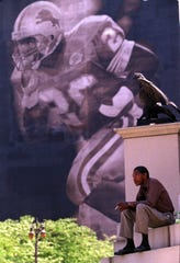 "Sylvester Smith takes his lunch break on the steps of the Soldiers and Sailors monument with the famous Barry Sanders mural in the background Wednesday, July 28, 1999. With the shocking news of Sanders retirement from football, Smith says ""the Lions are really loosing a good thing, the whole city is going to miss him."""