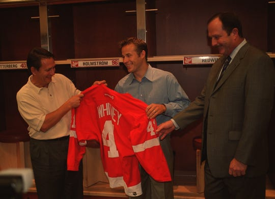 Red Wings forward Ray Whitney received his new his No. 41 jersey from general manager Ken Holland (left) and coach Dave Lewis (right) as he is introduced to the media on Aug. 6, 2003.