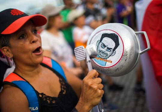 "A demonstrator bangs on a pot that has a cartoon drawing of Governor Ricardo Rossello and text the reads in Spanish ""Quit Ricky"" as people gather to protest against Gov. Rossello, in San Juan, Puerto Rico, Friday, July 19, 2019."