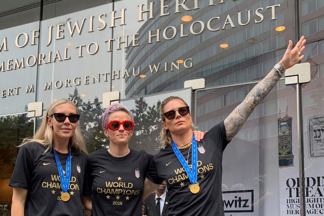 In this Wednesday, July 10, 2019 photo provided by Jeff Simmons, U.S. women's soccer player Ashlyn Harris raises her left arm next to her teammates, Allie Long and Megan Rapinoe, outside the Museum of Jewish Heritage before a victory parade in New York City, to celebrate the team's Women's World Cup title.