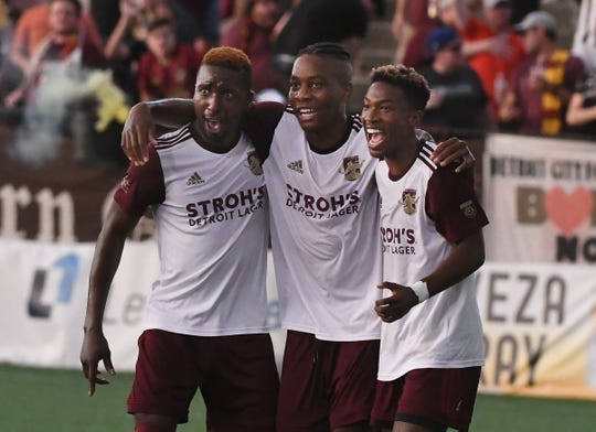 Detroit City FC's Shawn Lawson, center, celebrates his goal with teammates Tendai Jirira and Will Perkins in the first half of the 2-0 victory over Minneapolis SC in the  2019 NPSL Midwest Region semi-finals in Detroit, Michigan on July 19, 2019.
