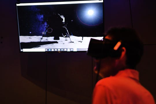 Scott Liefer of Bloomfield Hills wears a virtual reality headset as he views the lunar module for the 50th anniversary of the Apollo 11 moon landing at the Cranbrook Institute of Science on Saturday, July 20, 2019.
