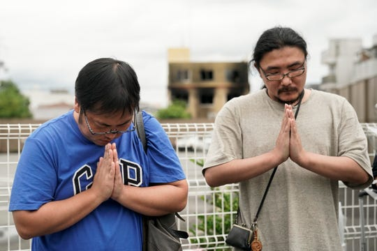 Two men pay respects at a makeshift memorial site to honor the victims of Thursday's fire at the Kyoto Animation Studio building, background center, Friday, July 19, 2019, in Kyoto, Japan.