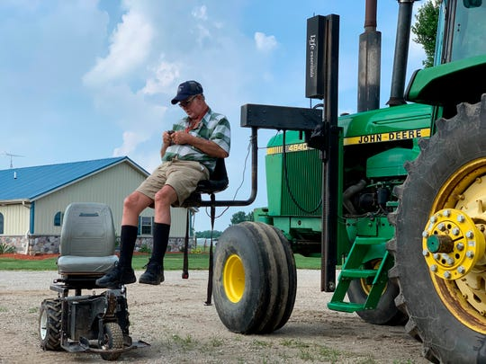 Farmer Mark Hosier, 58, uses a lift to get into a tractor on his farm in Alexandria, Ind. Hosier was injured in 2006, when a 2000-pound bale of hay fell on him while he was working.