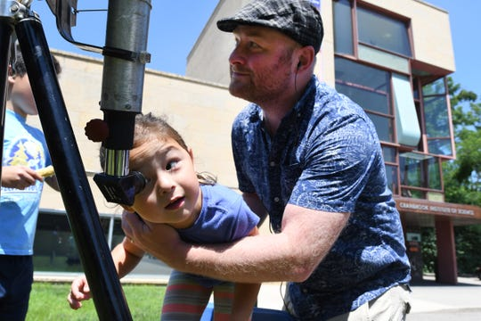 David Papa hold his daughter Jessica, 5, as she views the sun through a specialized telescope at the Cranbrook Institute of Science for the 50th anniversary of the Apollo 11 moon landing at the Bloomfield Hills campus on Saturday.