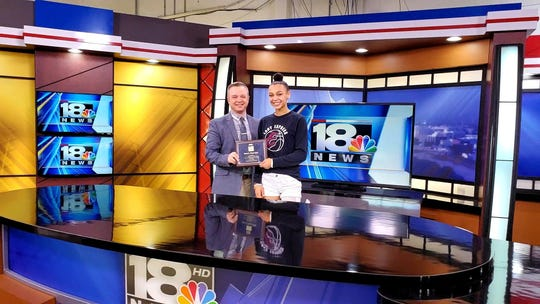 Elmira girls basketball standout Kiara Fisher appears on WETM-TV with Andy Malnoske to hold the Edward R. Murrow plaque.