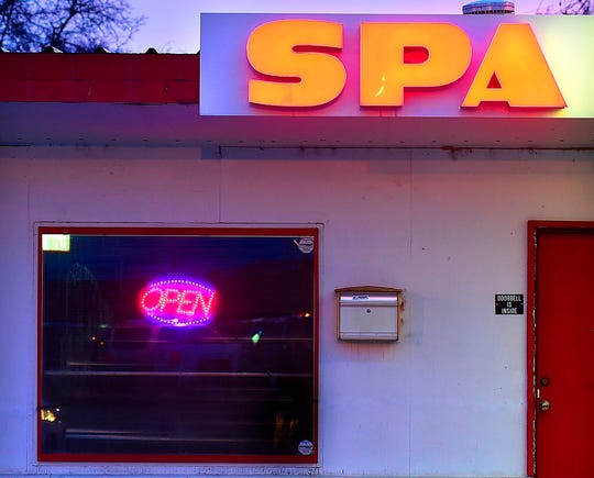 """This April 16, 2019 photo shows a massage outlet in Billings, Mont. Billings has a parlor problem. The businesses, which bill themselves as massage outlets but also offer commercial sex, according to law enforcement, have been an open secret in town for years, with their all-night neon """"open"""" signs and covered windows. (Larry Mayer/The Billings Gazette via AP)"""