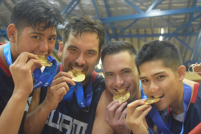 Team Guam test their gold medals after beating Fiji July 20 at the Pacific Games in Samoa.