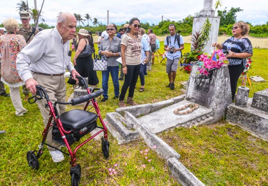 World War II veteran Raymond Faulkner, 97, stops briefly at the gravesite of Pedro Borja Pangelinan, during a visit to the Sumay Cemetery, located on Naval Base Guam, on Saturday, July 20, 2019. As part of the 75th Liberation celebration,  former residents of Sumay village, their descendants and others were able to attend a memorial Mass and luncheon at the cemetery.