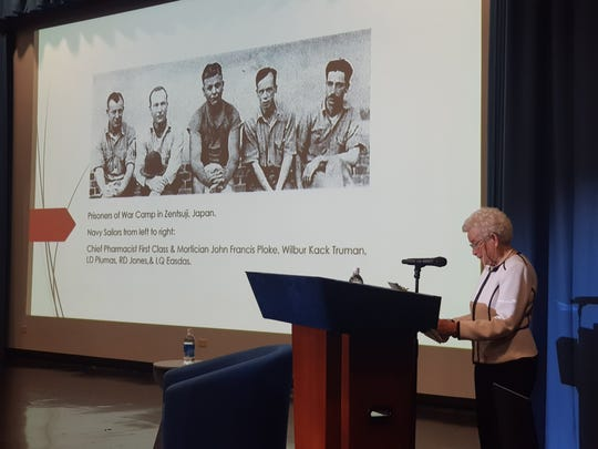 World War II survivor Irene Perez Ploke Sgambelluri speaks at the Guam Museum for the 75th Guam Liberation Lecture Series on July 20, 2019. On screen is a photo of her father, John Francis Ploke and other prisoners of war.