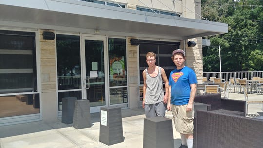Sean Frederick, left, and Travis Dillman stand outside Scotty's Dawghouse. A sign in the window announced today the company was ceasing all operations,   leaving the pair without jobs.