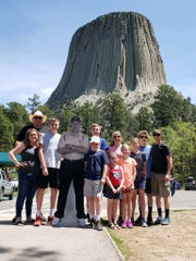 Kelly Kitchel and his family - with a cut-out of former coach Joe Tiller - in front of Devils Tower