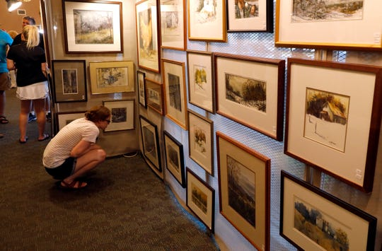 Erica Partridge squats down to look at paintings by Ed Kitchen Friday night, July 19, 2019, at Standing Stone Bank during the Lancaster Festival's annual ArtWalk in downtown Lancaster.