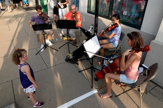 (left to right) Vincent Brausch, Lynne Theller-Kitchen, Hattie Poling and Bridget Brausch perform in front of the Ohio Glass Museum Friday night, July 19, 2019, in downtown Lancaster during the Lancaster Festival's annual ArtWalk.