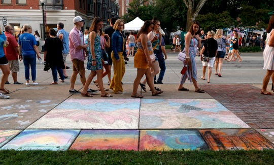 A group of people walk by chalk drawings on the sidewalks Friday, July 19, 2019, during the annual ArtWalk in downtown Lancaster. Thousands of people flooded downtown to enjoy the 32nd annual art and music tour.