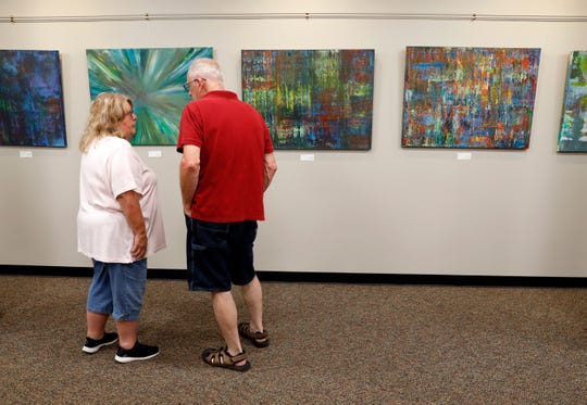 Kathy, left, and Harry Benson, from Lancaster, talk in front of artwork by Tamara Welch Friday night, July 19, 2019, in downtown Lancaster. Welch was showing her artwork for the first time at the ArtWalk.