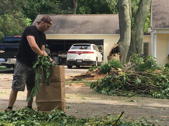 Brighton resident Nick Rosochacki cleans up debris on Madison Street in Brighton on Saturday July 20, 2019. He said he and his family have been without power since approximately 7:30 p.m. Friday. He and his dad Mike Rosochacki and uncle Don Rosochacki cleaned up debris in their neighborhood.