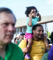 Story McElroy, 3, tries on her father Shelton's glasses as they attend Saturday's community walk against racism at the Big Four Bridge. The event drew hundreds, after racist graffiti was discovered July 10 on the Big Four Bridge.