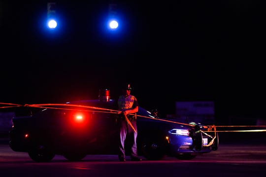A Michigan State Trooper tapes off the intersection of Old U.S. 127 and Round Lake Road near south of a multiple-vehicle crash at the Cutler Road intersection on Friday, July 19, 2019, in DeWitt Township.