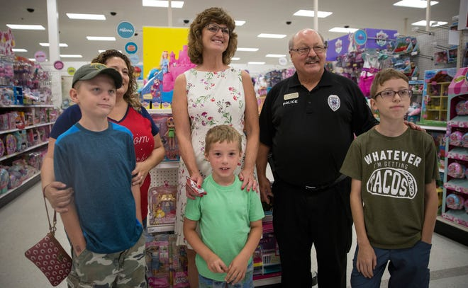 Muncie Community School's new CEO Lee Ann Kwiatkowski stands for a photo with a family she was helping shop with along with Chuck Hensley, one of the organizers for the event with the annual Back to School Heroes and Helpers program.