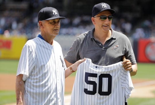 Astronaut Mike Massamino, right, poses for photographs with former New York Yankees pitcher Jack Aker before a baseball game between the New York Yankees and the Colorado Rockies Saturday, Jan. 20, 2019, in New York.