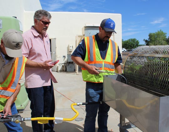 Randy McMillan, owner of The Fresh Chile Company, center, stands by as Las Cruces Utilities' Jeff Griffith lights the flame and LCU Gas Pressure & Service Supervisor Andy Sanchez adjusts the natural gas.
