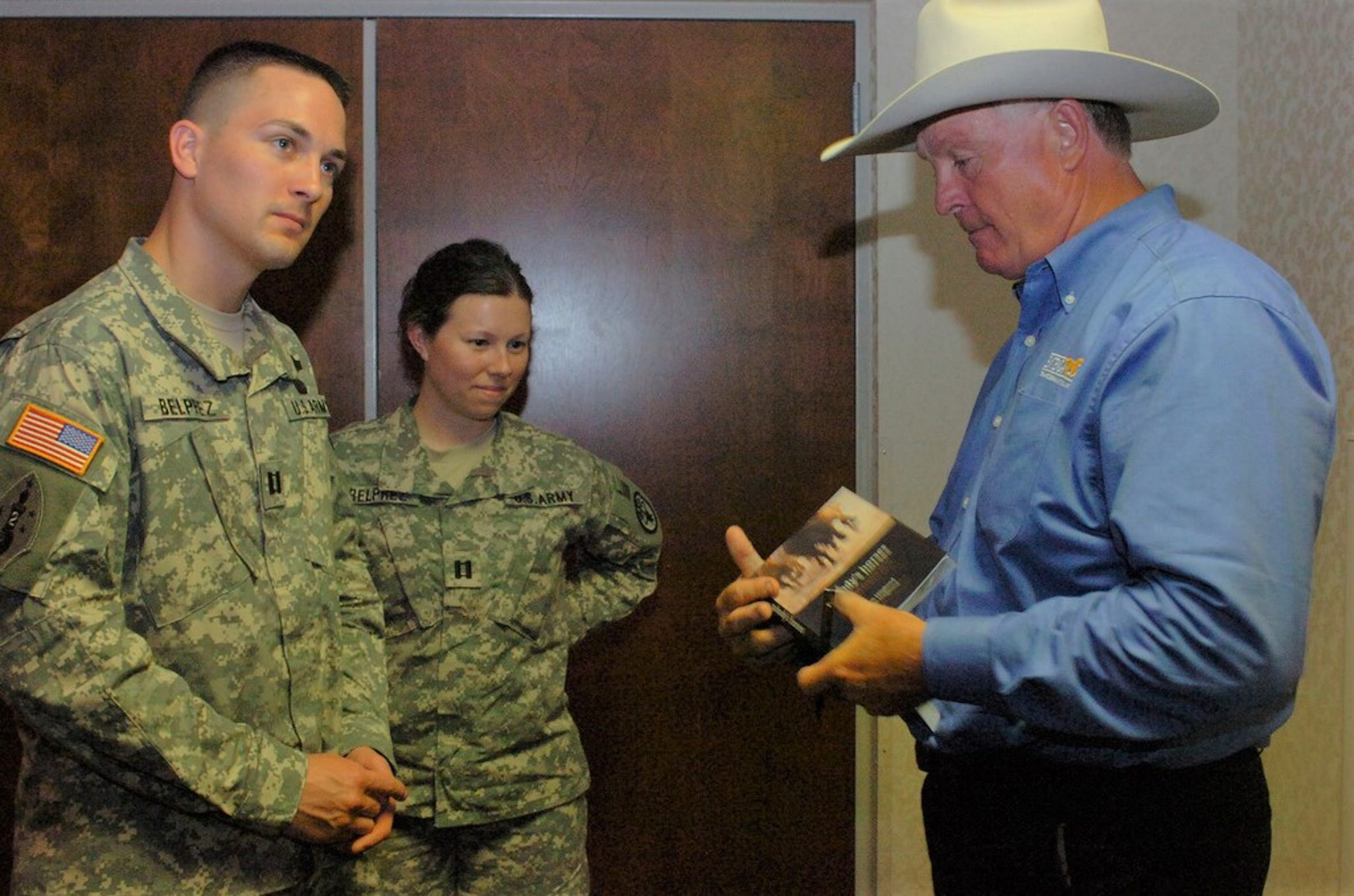 "Capt. James Belprez, left, and his wife, Capt. Megan Belprez, watch as Don Hoglund signs a copy of his book ""Nobody's Horses"" for them during at appearance at Fort Bragg North Carolina in this undated photo."