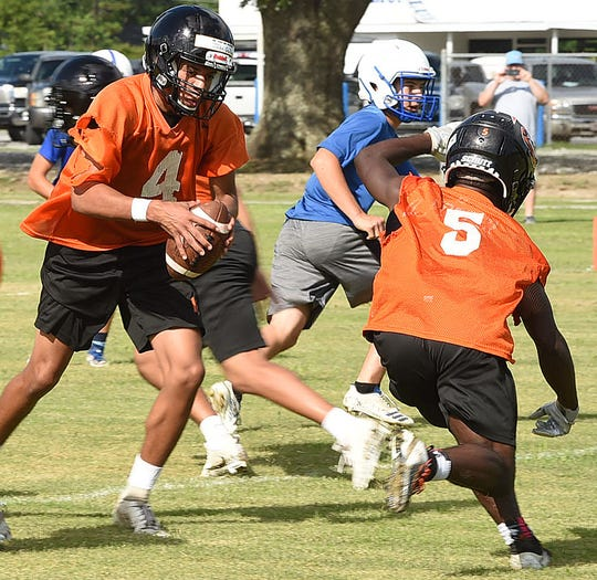 Opelousas High quarterback John Guilbeau (4) hands off the ball during a seven-on-seven game Thursday at St. Edmund in Eunice. The Tigers start a third season under head coach Doug Guillory.