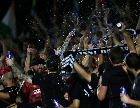 Phoenix Rising fans let the beer fly on dollar beer night after their Rising's scored their third goal against Austin Bold during the second half at Casino Arizona Field in Scottsdale July 19, 2019. (Darryl Webb/For the Republic)