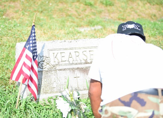 A volunteer works to clean up the grave of a veteran at Lebanon Cemetery in North York on Saturday, July, 20.