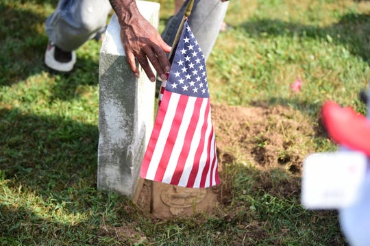 A volunteer plants an American flag by the grave of a veteran at Lebanon Cemetery in North York on Saturday, July, 20.