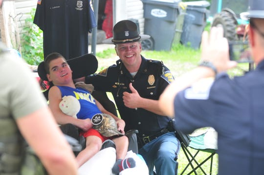 Indiana State Police Master Trooper Kyle West poses with Jeremiah Lehman after Lehman received a some gifts, including a hat, from the Indiana State Police officers who visited him Saturday, July 20, 2019.
