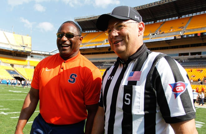 Syracuse head coach Dino Babers, left, talks with an official before a 2018 game against the Pittsburgh Panthers at Heinz Field. Pittsburgh won 44-37 in overtime.