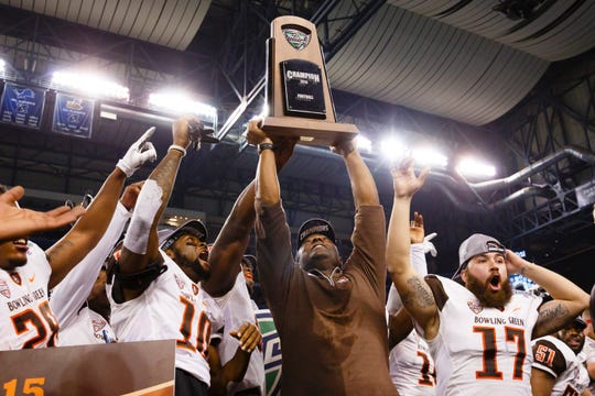 Bowling Green Falcons head coach Dino Babers holds up the trophy after winning the MAC Championship against the Northern Illinois Huskies at Ford Field in Detroit. Bowling Green won 34-14.