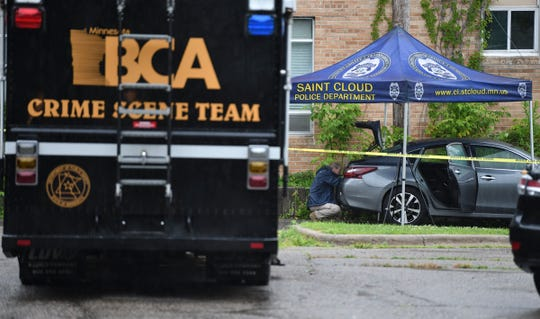 A vehicle is photographed at the crime scene in the alley in the 300 block between Fourth Avenue South and Fifth Avenue South Saturday, July 20, 2019, in St. Cloud.