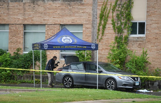 An investigator photographs a vehicle in a crime scene in the alley in the 300 block between Fourth Avenue South and Fifth Avenue South Saturday, July 20, 2019, in St. Cloud. St, Cloud police say a 24-year-old man was shot in the driver's seat of a vehicle and later died at the St. Cloud Hospital.