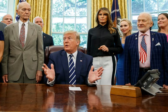 President Donald Trump, accompanied by Apollo 11 astronauts Michael Collins, left, and Buzz Aldrin, right, with Vice President Mike Pence and first lady Melania Trump, speaks during a photo opportunity commemorating the 50th anniversary of the Apollo 11 moon landing, in the Oval Office of the White House, Friday, July 19, 2019, in Washington.