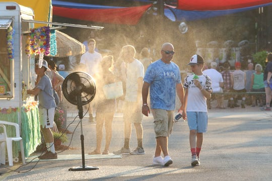 Attendees at the Delaware State Fare cool off during a heatwave on Friday.