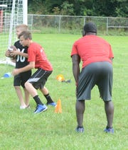 Logan Wilhite (red) practices tackling Kasey Britton (black) during a linebacker drill with former Ohio State Buckeye Brian Rolle during Saturday's Future Stars Football and Cheer Camp at Rosecrans High School.