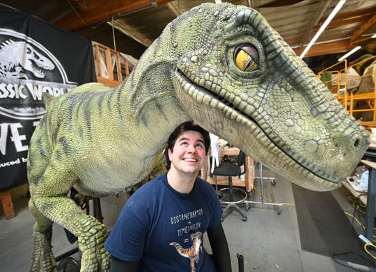 "Robert Gardner is clearly a fan of dinosaurs. Here, he poses with one of the animals he controls in the ""Jurassic World Live Tour."""