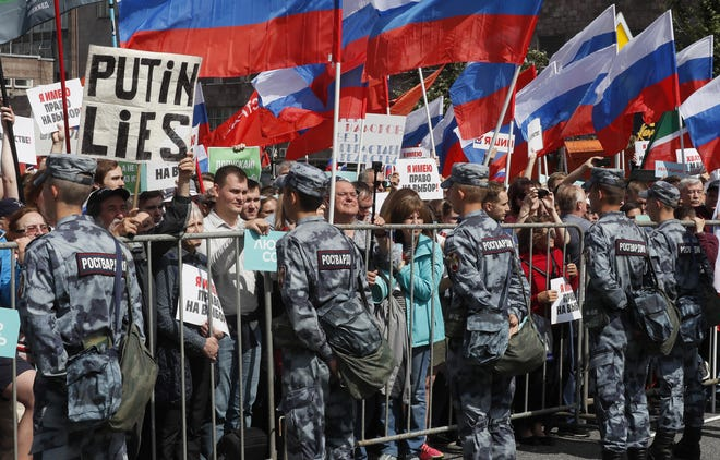 Russian opposition supporters hold a poster 'Putin lies' during a rally in support of opposition candidates in the Moscow City Duma elections in downtown Moscow, Russia, July 20, 2019. Russian opposition supporters dissatisfied with the fact that the district election commissions rejected signatures for independent candidates in the Moscow City Duma elections.