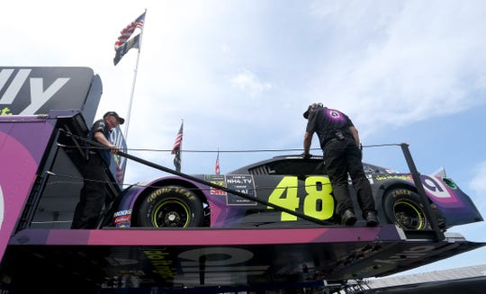 Hendrick Motorsports crew members take out Jimmie Johnson's backup car Saturday to prepare it for Alex Bowman.