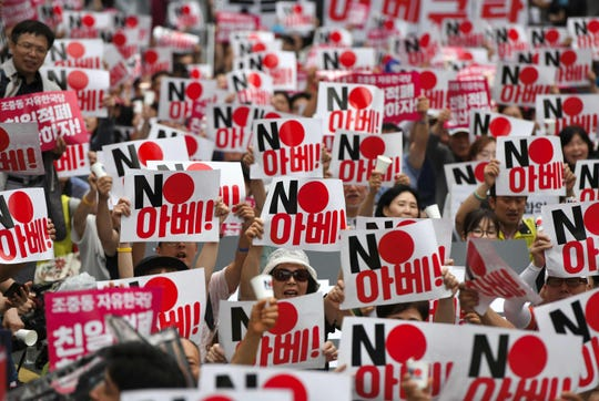 """South Korean protestors hold up placards reading """"No Abe!"""" during a rally denouncing Japan for its recent trade restrictions against Seoul over wartime slavery disputes, near the Japanese embassy in Seoul on July 20, 2019. An elderly South Korean man died on July 19 after setting himself on fire outside the Japanese embassy in Seoul as a bitter diplomatic dispute over wartime forced labour compensation took a fatal turn. Japan this month unveiled tough restrictions on exports crucial to tech titans like Samsung, fueling fears about the impact on the global tech sector, while South Korea's central bank warned it could have """"no small impact"""" on the economy."""