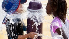 Children put their faces in a fountain at a water park during an excessive heat watch in Washington, on July 19, 2019. An excessive heat watch has been issued for the weekend in Washington DC.