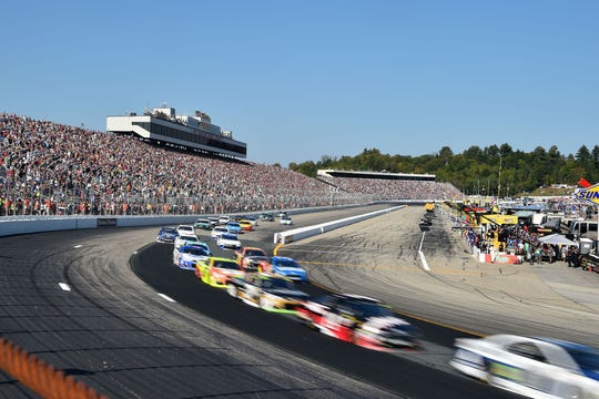 NASCAR Cup cars race around the oval at New Hampshire Motor Speedway.