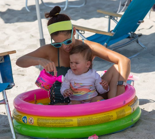 A mom and child use a kiddie pool to cool off as they visit Ortley Beach in the heat on July 21, 2019.