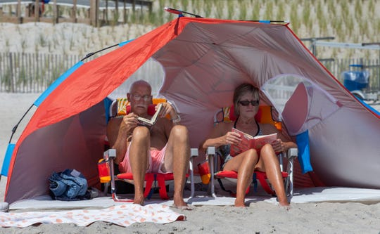 A couple use a tent to keep in the shade as they read on the beach in Ortley on July 21, 2019.